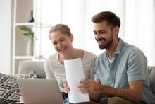 Happy Husband And Wife Read Good News Online At Laptop, Millennial Couple Smiling Holding Documents Receiving Positive Decision From Bank, Man And Woman Get Email Having Mortgage Or Loan Approved