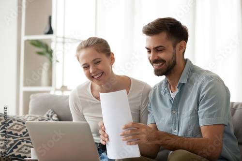 Fotografía  Happy husband and wife read good news online at laptop, millennial couple smilin