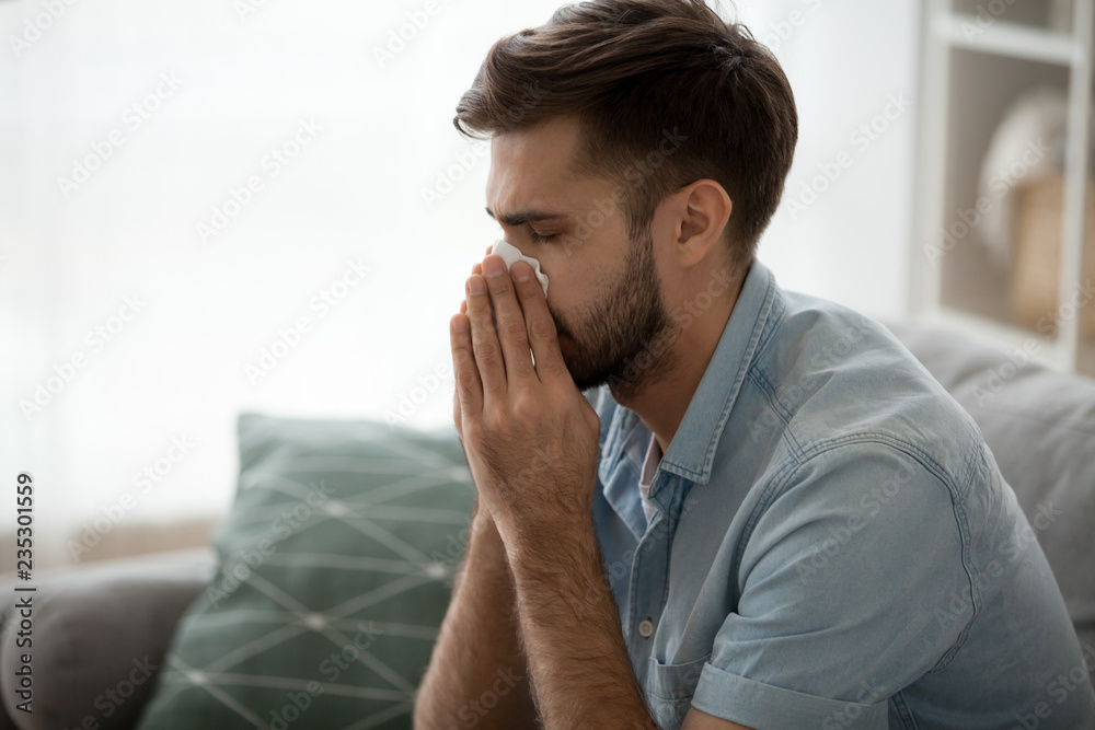 Fototapety, obrazy: Ill millennial man sit on couch feel unwell blowing running nose with napkin, sick male at home have health problems, get flu or fever symptoms, tired guy suffer from sickness sneezing holding tissue