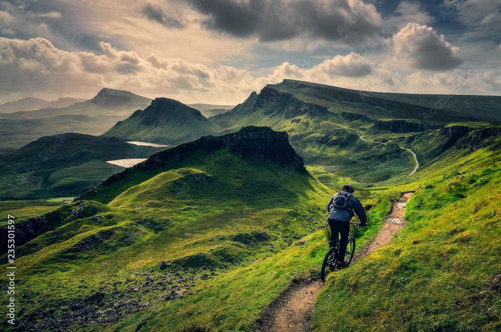 Fototapeta Mountain biker riding through rough mountain landscape of Quiraing, Scotland