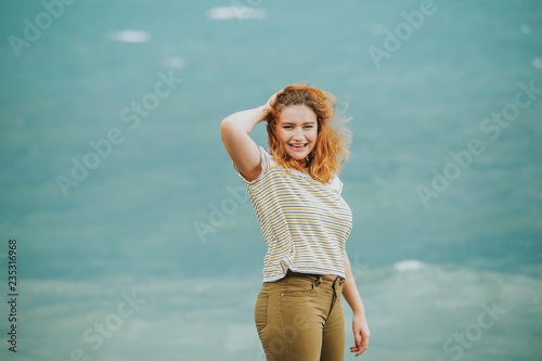 Fotografia  Outdoor portrait of young woman next to storm lake on a windy day