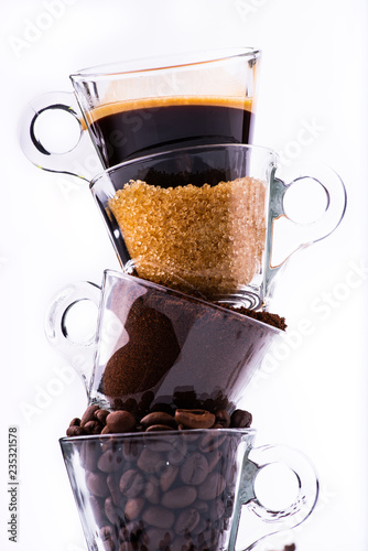Photo  glass cups, in vertical sequence, with coffee beans, ground coffee, brown sugar and a creamy drink