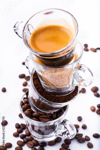 glass cups, in vertical sequence, with coffee beans, ground coffee, brown sugar and a creamy drink Canvas Print