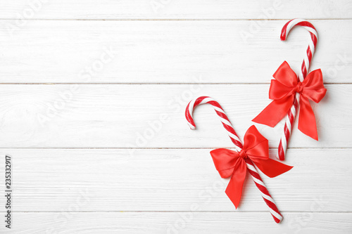Flat lay composition with tasty candy canes and space for text on wooden background