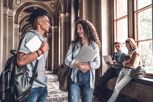 The best friends.Young smiling students standing in the university hall and speak with each other.