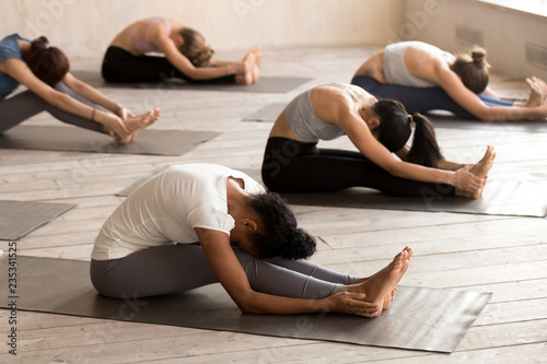 Fotobehang School de yoga Group of young people doing yoga Seated forward bend exercise, paschimottanasana pose, working out, indoor full length, mixed race female students training at club. Well being, wellness concept