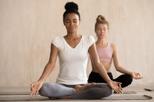 Two Beautiful Diverse Yogi Girls Doing Yoga Padmasana Exercise, Lotus Pose With Mudra, Working Out, Indoor Full Length, Mixed Race Female Students Training At Club. Well Being, Wellness Concept