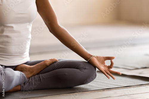 Obraz Yogi black woman practicing yoga lesson, breathing, meditating, doing Ardha Padmasana exercise, Half Lotus pose with mudra gesture, working out, indoor close up. Well being, wellness concept - fototapety do salonu