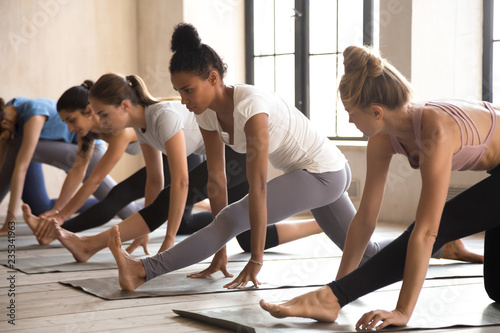 Fotografija  Group of young diverse sporty people doing yoga Half splits exercise, Ardha Hanumanasana pose, working out indoor, mixed race female students training at club or studio