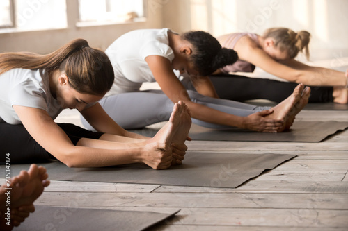 Fotografía  Group of diverse young people practicing yoga lesson, doing Seated forward bend exercise, paschimottanasana pose, mixed race female students training at sport club