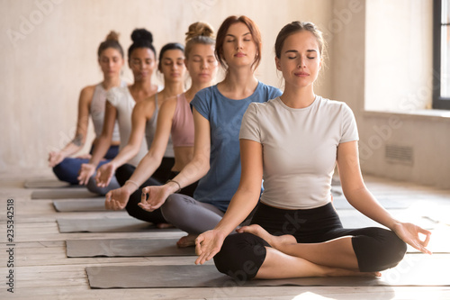 Recess Fitting Yoga school Group of diverse young people practicing yoga, doing Easy Seat exercise, Sukhasana pose, working out indoor full length, female students meditating at club or yoga studio. Well being, wellness concept