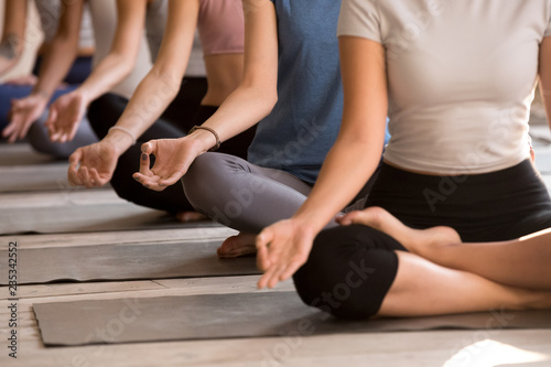 Fotobehang School de yoga Group of diverse young yogi people meditating, Easy Seat exercise, doing yoga Sukhasana pose, working out indoor close up, female students training at club or yoga studio. Well being, wellness concept