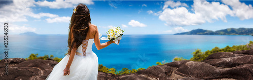 Fotografie, Obraz  bride, beautiful young girl with dark hair in a white wedding dress with bouquet on  background of beach with blue water