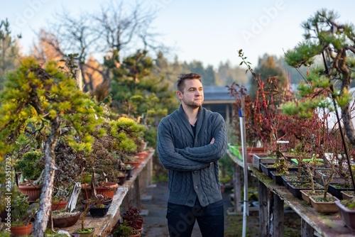 Young man bonsai artist in his bonsai farm