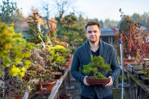 Young man bonsai artist in his bonsai farm