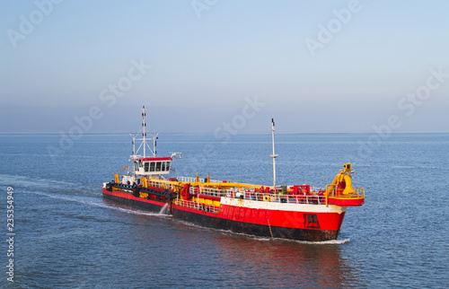 Valokuva  Red dredging vessel working on sea, removing sediment in a waterway