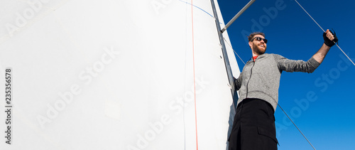 Fotomural Yacht captain with a beard stands on sail boom on a sailing yacht, holding the rope in his hand and smiling, feeling happy