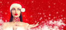 Christmas Woman. Joyful Model Girl In Santa's Hat With Lollipop Candy Pointing Hand, Proposing Product. Sales. Surprised Expression. Closeup Portrait Isolated On Red Background