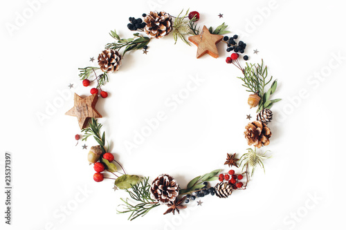 Christmas circle floral composition. Wreath of cypress, eucalyptus branches, pine cones, rowan berries, anise, confetti stars and sea holly flowers on white background. Winter wedding design. Flat lay