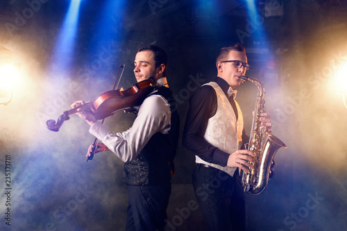 Photo  Saxophonist and violinist playing classical music