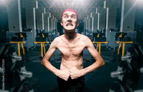 Fotomural Thin guy poses on workout in gym, dystrophic