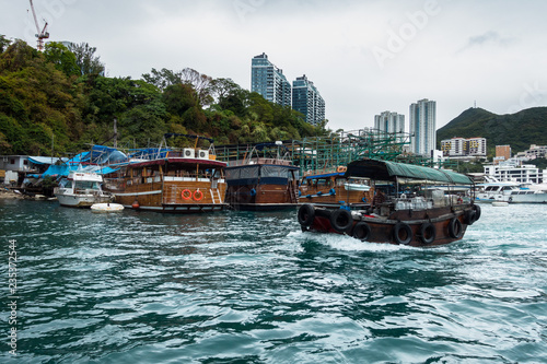 Photo A sampan in Aberdeen habour, with typical house boats on the background, Hong Ko
