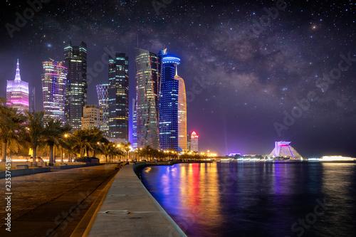 Fototapeta Oświetlone miasto Doha w Emiracie w Katarze wieczorem z rozgwieżdżonym niebem