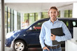 Salesman with clipboard near new car in modern auto dealership