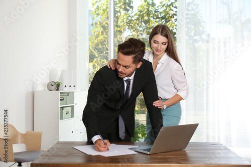 Fotografija  Woman molesting her male colleague in office