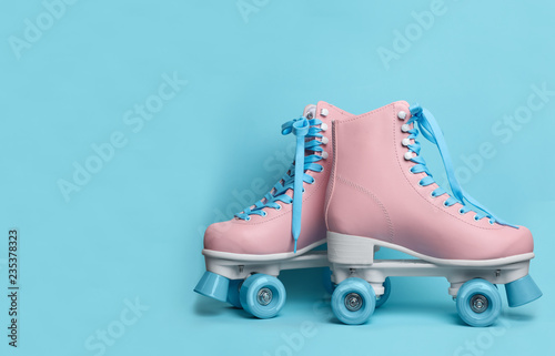 Pair of stylish quad roller skates on color background. Space for text