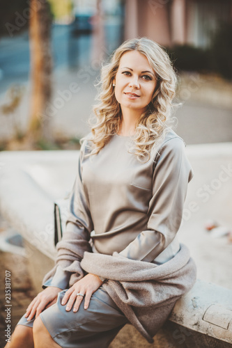 Photographie  Fashion portrait of beautiful blond woman wearing silk classy dress, posing outd