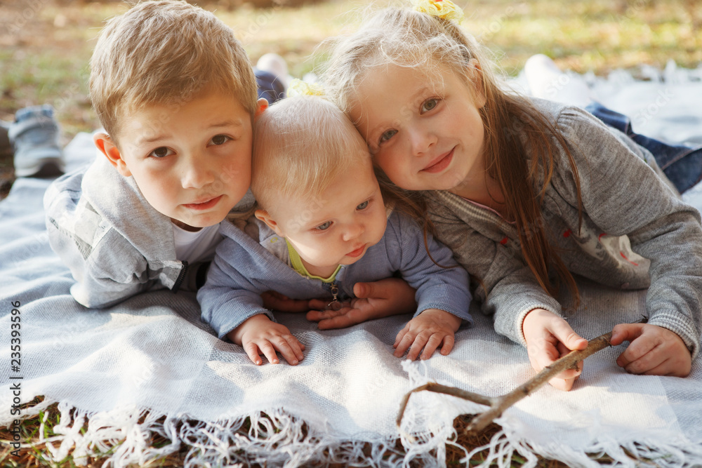 Fototapety, obrazy: Three children, elder brother, sister blonde and 7-month-old boy with blue eyes are lying on a rug in the autumn forest.