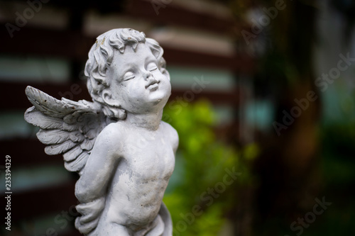 Photo closeup cupid sculpture in garden with soft-focus and over light in the backgrou