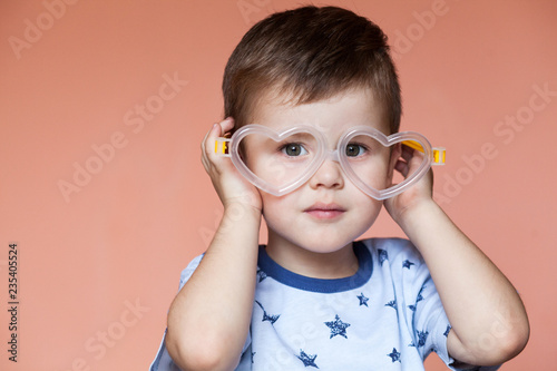 Valokuva  Portrait of cute little boy wearing heart shaped glasses