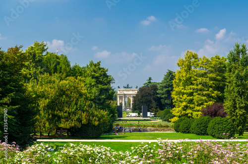 Arch of Peace gate and green trees, grass lawn in park, Milan, Italy