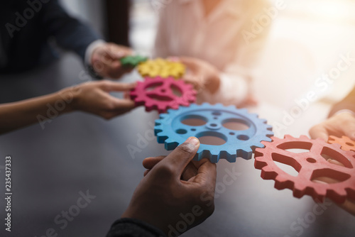 Obraz Business team connect pieces of gears. Teamwork, partnership and integration concept - fototapety do salonu