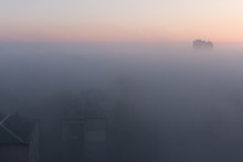 Buildings In Morning Haze. Panoramic View Of Misty City. Foggy Cityscape. Scenic Winter Landmark. Sunset And Fog Over City Buildings. Aerial Background.