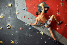 Sporty Strong Young Man With Tanned Muscular Naled Torso Exercising In Boulder Climbing Hall Reaching New Results, Enjoying New Challenges.