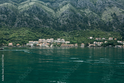 Beautiful view from the sea on the coastal town near the mountain in Montenegro.