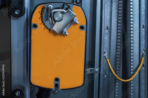 Valokuvatapetti Orange damper actuator installed on the industrial ventilation unit body, front