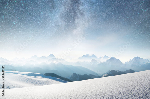 Mountains and sky with stars. Natural landscape in mountains region at the winter time. Starry sky and high peak.