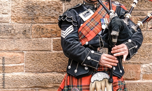 Photo EDINBURGH, SCOTLAND, 24 March 2018 , Scottish bagpiper dressed in traditional red and black tartan dress stand before stone wall