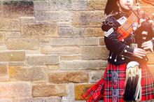 EDINBURGH, SCOTLAND, 24 March 2018 , Scottish Bagpiper Dressed In Traditional Red And Black Tartan Dress Stand Before Stone Wall. Edinburgh, The Most Popular Tourist City Destination In Scotland.