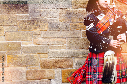 Leinwand Poster EDINBURGH, SCOTLAND, 24 March 2018 , Scottish bagpiper dressed in traditional red and black tartan dress stand before stone wall