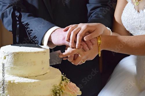 Braut und Bräutigam schneiden gemeinsam die Hochzeitstorte an Canvas Print