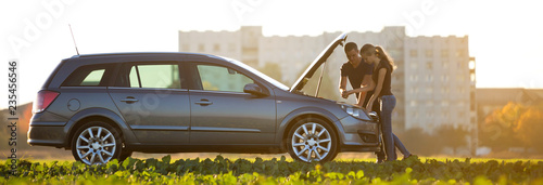 Fotografiet Young couple, handsome man and attractive woman at car with popped hood checking oil level in engine using dipstick on clear sky background
