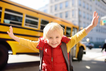 Pupil With Schoolbag With Yellow School Bus On Background