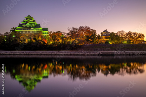 Foto night view of Okayama Castle by river asahi in japan