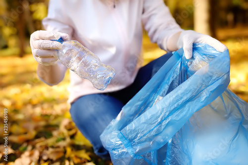 Volunteer picking up the garbage and putting it in biodegradable trash-bag on outdoors Canvas Print