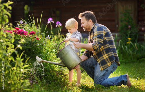 Middle age man and his little son watering flowers in the garden at summer sunny Fototapet